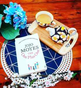 The One Plus One book by Jojo Moyes next to a cup of tea